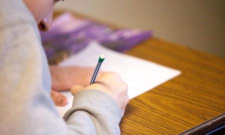Studente che scrive con una matita