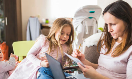 Donna che lavora al computer, attorniata dai figli
