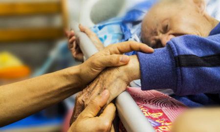 Infermiere che tiene la mano di un paziente