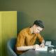 Giovane che scrive seduta alla scrivania